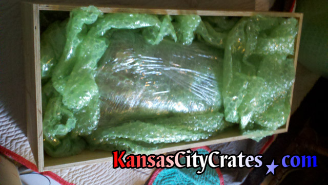 Neon sign bubble wrapped inside vault like wood crate for shipping.