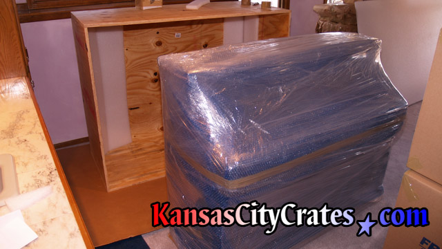 Paper wrapped, bubble wrapped and stretch wrapped Sauter piano before loading into export crate.