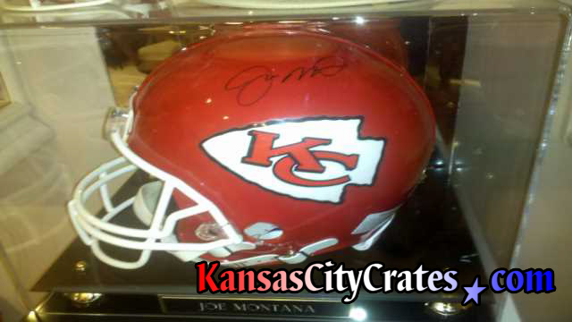Autographed helmet in glass case before wrapping and shipping in wooden box crate.
