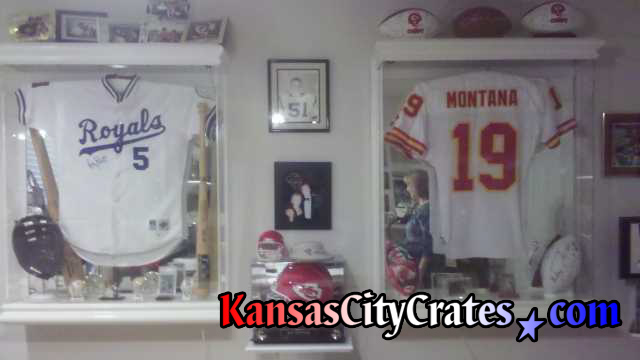 2 Glass cases containing Baseball jersey of George Brett and Football jersey of Joe Montana, both autographed, being packed into wood crate for storage.