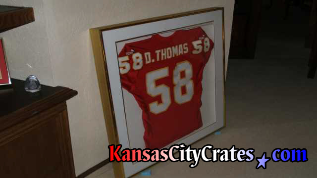 Crating Derrick Thomas football jersey in glass case.