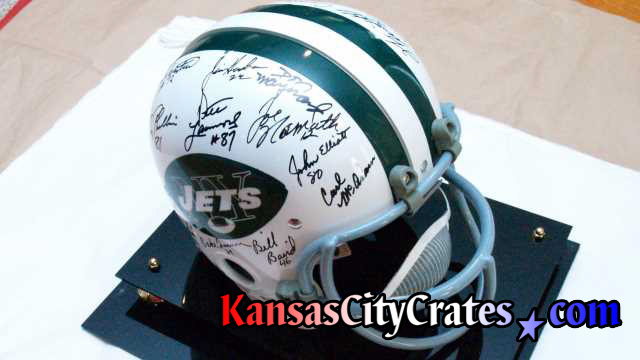Superbowl III winners showing Joe Namath's autograph on paper for packing into export crate.