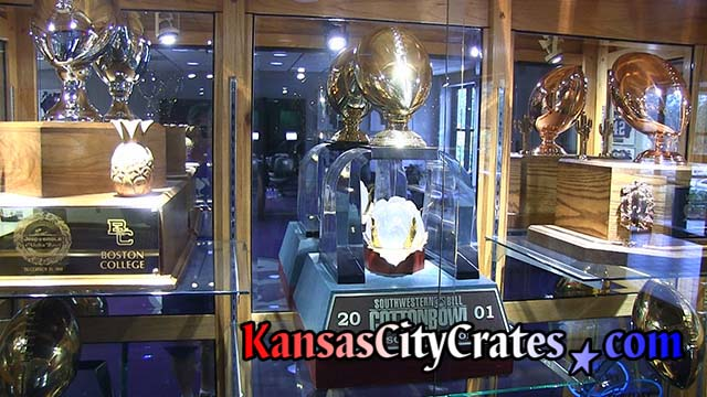 Glass cabinet with large trophies on display at Football Complex