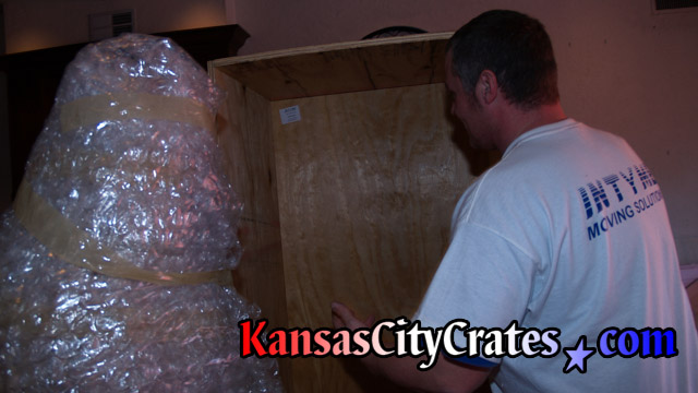 Bubble wrapped American Indian Chief statue loading into export crate for storage.