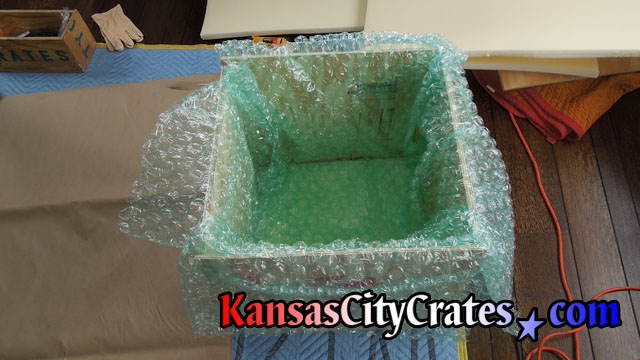 Additional layers of bubble wrap are placed in foam cushioned solid wall wooden crate to protect Robin's nest antique vase