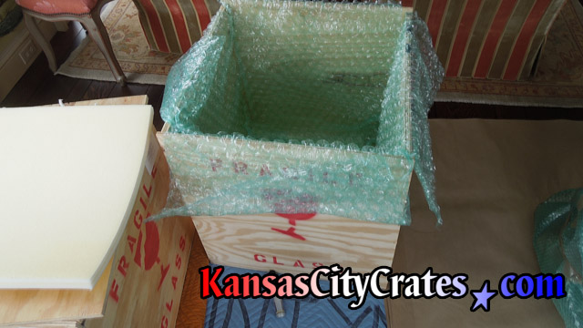 Foam cushioning is placed on bottom of wood crate before bubble wrap is layed inside.