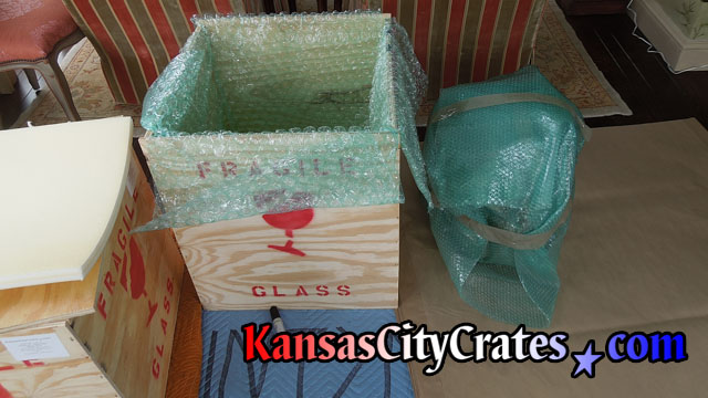 Tea pot wrapped in small bubble wrap before placing into foam lined crate layed with large bubble wrap.