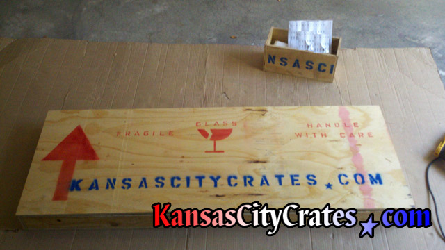 Marble top sealed in wood crate with shipping symbols to aid handlers during transport.