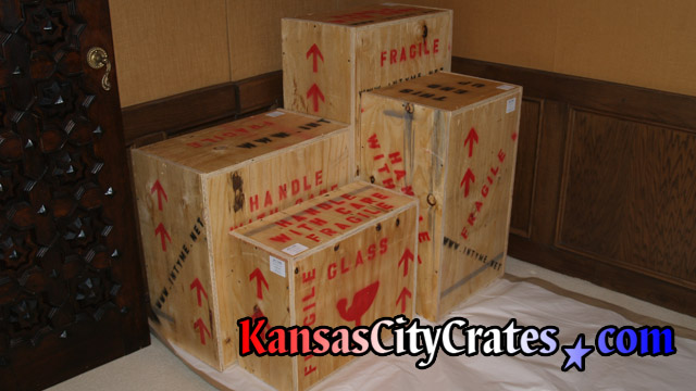 Four wood boxes containing artwork and glassware packed at home in Kansas City for storage.