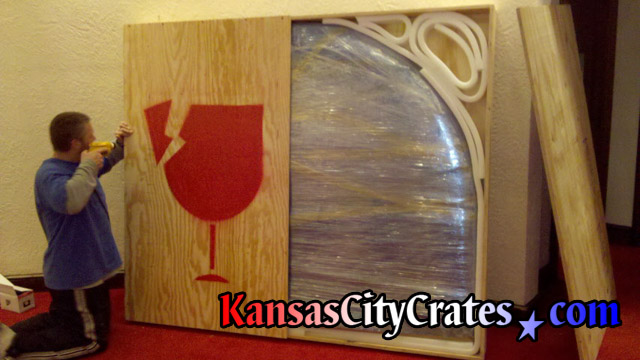 Attaching lid on large wood crate for stained glass window behind bar in suite at Arrowhead Stadium Kansas City MO