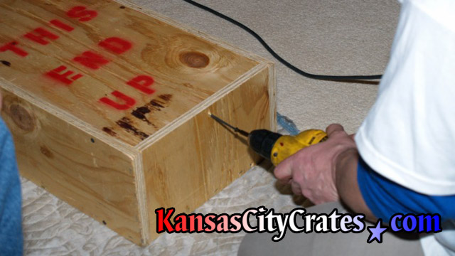 Additional screws are added to lid sealing wood crate closed.