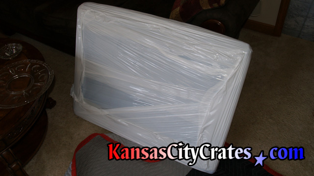 Example photos of different items that have it's paper and bubble wrap packaging secured with plastic stretch wrap to ease handling of object while loading or unloading crate that also provides a moisture barrier.