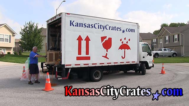 Crate builder assembles crate at business in St Joseph MO  64501 with truck guarded by orange traffic safety cones