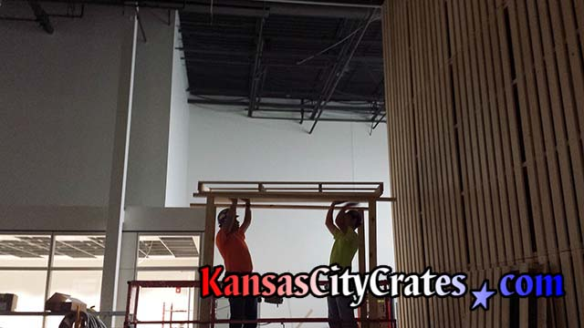 JE Dunn Construction employees raising pallet built by Kansas City Crates