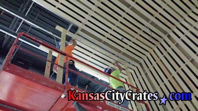 JE Dunn Construction employees installing pallet built by Kansas City Crates for Helix Architecture and Design