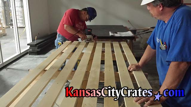 JE Dunn Construction employees adding lights to installing pallet built by Kansas City Crates for Helix Architecture and Design