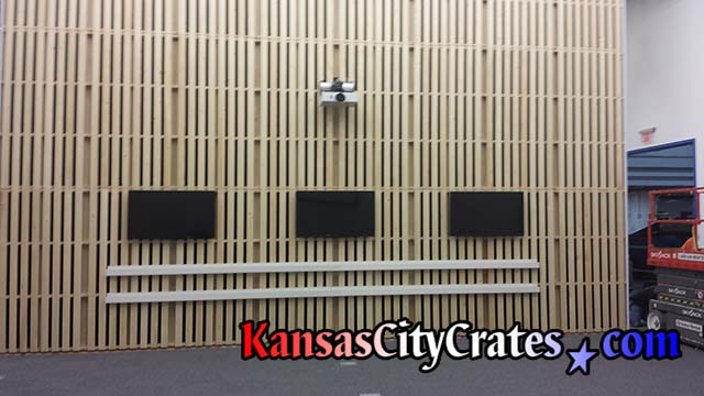 Flat screen monitors and projector mounted on pallet wall