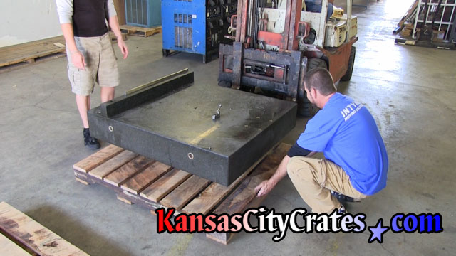 Positioning rough oak pallet under granite machine base for forklift.