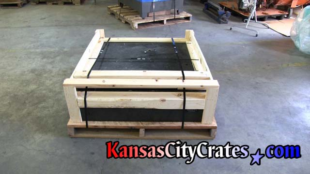 Granite machine top on rough oak pallet with open frame style crate steel strapped with double notch seals before stretch wrapping.