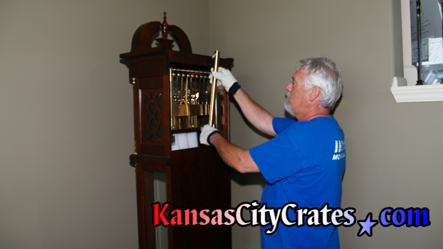John removing tubular chime from back of clock