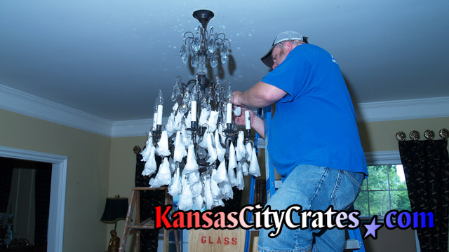 Packing fragile crystals on chandlier before removing from ceiling to hang in crate.